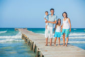 Família de quatro no cais pelo oceano — Fotografia Stock