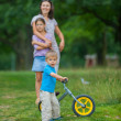 Little boy on a bicycle and his mother and sister — Stock Photo #9256018