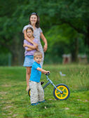 Little boy on a bicycle and his mother and sister — Stock Photo