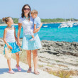 Family of three walking along tropical beach — Stock Photo #9269238
