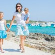 Family of three walking along tropical beach — Stock Photo #9294173