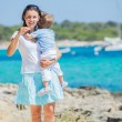 Family walking along tropical beach - Stock Photo