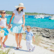 Family of three walking along tropical beach — Stock Photo #9294230