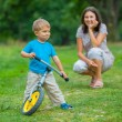 Little boy on a bicycle and his mother — Foto Stock