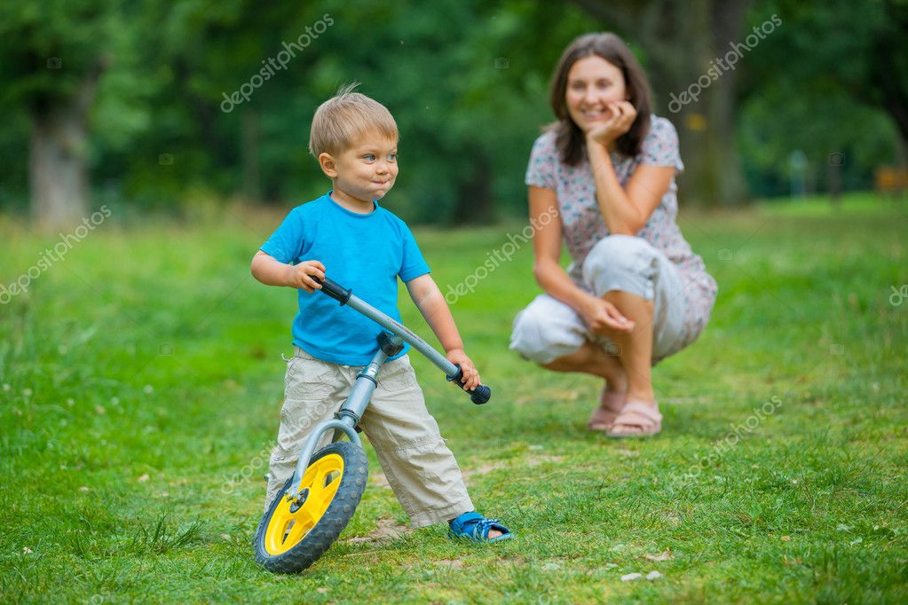 Portrait of little boy on a bicycle and his mother in the summer park — Stock Photo #9294801