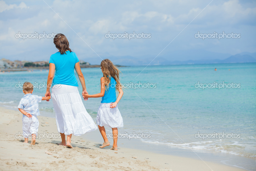Back view of mother and two kids having fun on tropical beach — Stock Photo #9307423