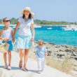 Family of three walking along tropical beach - Stock Photo