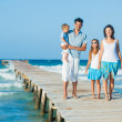 Family of four on jetty by the ocean — Stock Photo