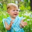 Little girl sitting in the grass in the park — Stock Photo
