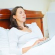 Smiling woman using laptop sitting in bed — Stock Photo #9383483