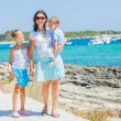 Family of three walking along tropical beach — Stock Photo