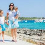Family of three walking along tropical beach — Stock Photo #9388442