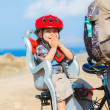 Child sitting by bicycle in crash helmet — Stock Photo #9686695