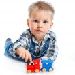 Cute little boy playing trains — Stock Photo