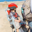 Child sitting by bicycle in crash helmet — Stock Photo
