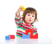 Smiling little girl is building — Stock Photo