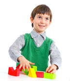 Smiling little boy is building — Stock Photo