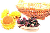 Hibiscus on a wooden spoon, flowers and wicker basket — Stock Photo