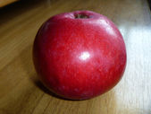 Red apple rests upon table — Stock Photo