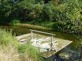 Wooden raft on stream — Stock Photo