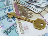 Key rests upon money bill — Stock Photo