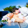 Groom and bride kissing on a car cowl - Stock Photo