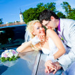 Groom and bride kissing on a car cowl — Stock Photo