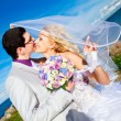 Stock Photo: Tender kiss of happy groom and bride on a sea coast