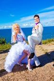 Happy groom and bride on a sea coast — Stock Photo
