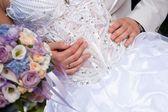 Hands of groom gently embracing brides's waist — Stock Photo