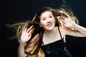 Cute girl lasting towards to wind and light on black — Stock Photo