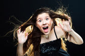 Cute girl with dark long hair shouting on black — Stock Photo