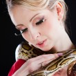 Attractive blond woman with python on black — Stock Photo