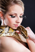 Attractive nude blond woman with python on black — Stock Photo