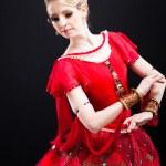 Ballerina wearing red tutu posing on black — Stock Photo #10343754