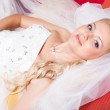 Beautiful bride lying on red sofa — Stock Photo #10538878