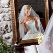Beautiful bride in white in front of mirror — Stock Photo