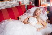 Beautiful bride lying on red sofa — Stock Photo