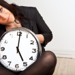 Stock Photo: A Tired Woman Holding a Clock