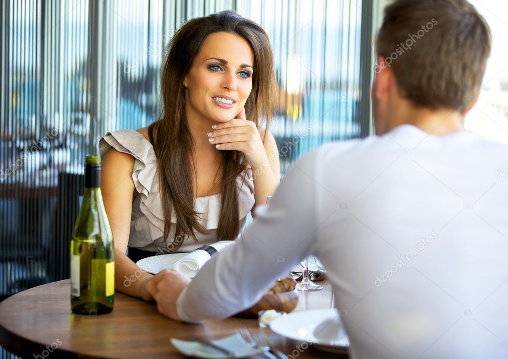 Portrait of a gorgeous woman holding hands with her boyfriend at a fancy restaurant — Stock Photo #10457287