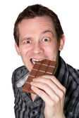 Man eating a mighty hard chocolate — Stock Photo