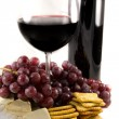Bottle of red wine with some grapes — Stock Photo