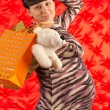 Portrait of a young pregnant woman with shopping on red backgrou — Stock Photo