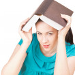 Stock Photo: Womin blue dress hid behind book