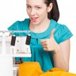 Girl in blue dress on sewing machine darning — Stock Photo #9315087