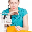 Girl in blue dress on sewing machine darning — Stock Photo #9315101