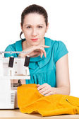 Girl in a blue dress on the sewing machine darning — Stock Photo