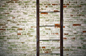 Old metal ladder with brick wall — Stock Photo