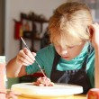 Little girl is painting handmade clay sculpture — Stock Photo