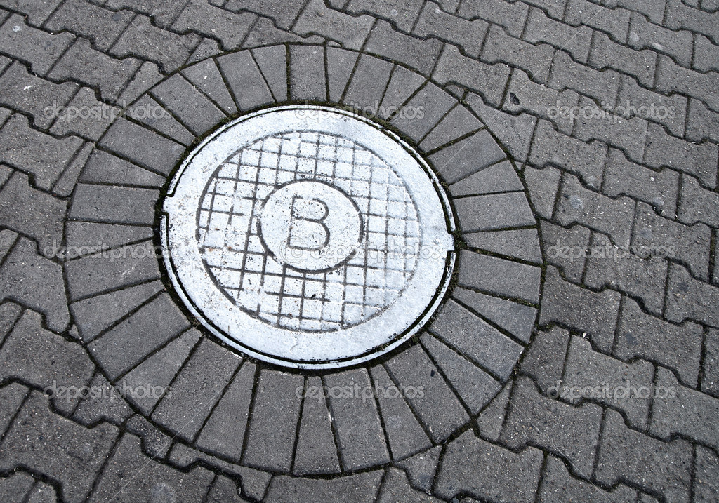 White sewer manhole marked with B sign on the cobblestone road — Stock Photo #8782585